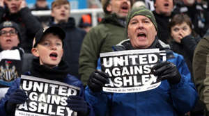 a group of people holding a sign:                      We call it the beautiful game, but sometimes it gets ugly.                                                                              From spats between team-mates and coaches to fans taking aim at owners and governing bodies, we've put together the ultimate collection of footballing feuds from the 21st century.