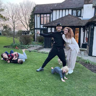 a group of people playing frisbee in a yard: Stacey Solomon and her family moved into their new home in March