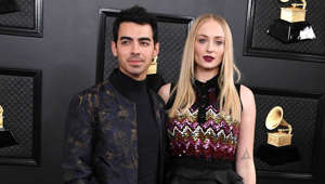 a person standing in front of Joe Jonas, Sophie Turner posing for the camera