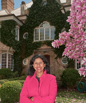 a woman wearing a pink flower is standing in front of a building: Usha Subramaniam, a real estate broker for Compass, listed a home in Mount Kisco, N.Y. She says pricier homes used to linger on the market for years.