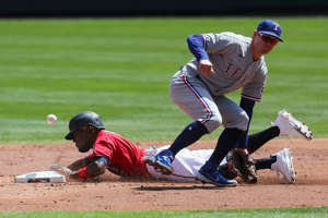 a baseball player pitching a ball on a field: May 6: The Minnesota Twins' Nick Gordon steals second against the Texas Rangers in the second inning at Target Field. The Rangers won the game, 4-3, in 10 innings.