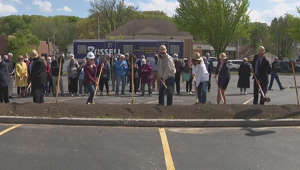 a group of people standing on the side of a road: Construction begins on new East Moline library after groundbreaking ceremony