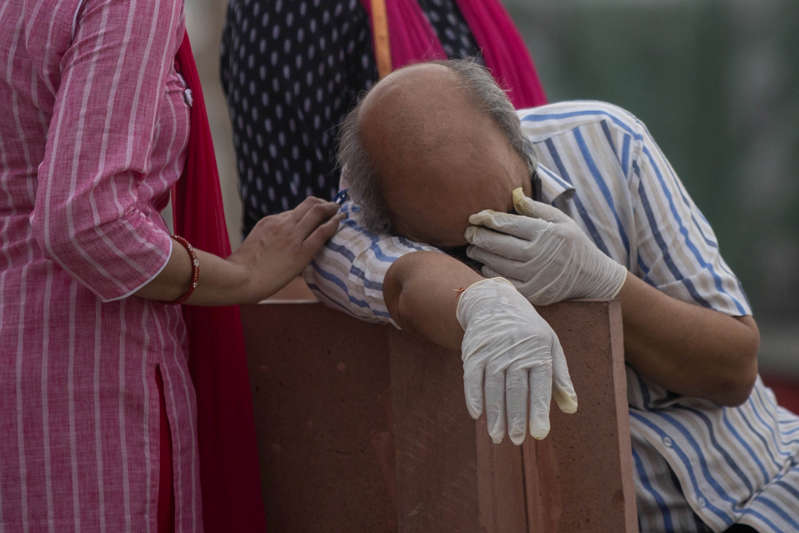 A man reacts before the cremation of his relative, who died from the coronavirus disease (COVID-19), on the banks of the river Ganges at Garhmukteshwar in the northern state of Uttar Pradesh, India, May 6, 2021. REUTERS/Danish Siddiqui
