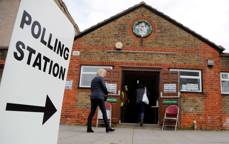 People queue at the entrance of a polling station in London, Thursday, May 6, 2021. Millions of people across Britain will cast a ballot on Thursday, in local elections, the biggest set of votes since the 2019 general election. A Westminster special-election is also taking place in Hartlepool, England.(AP Photo/Frank Augstein)