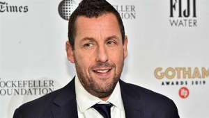 Adam Sandler wearing a suit and tie smiling at the camera