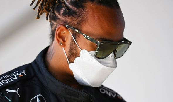 a person wearing a mask: Lewis Hamilton