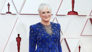 Glenn Close standing in front of a blue dress
