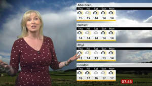 Carol Kirkwood holding a cell phone screen with text: Breakfast: Carol Kirkwood tells Louise Minchin 'old saying'