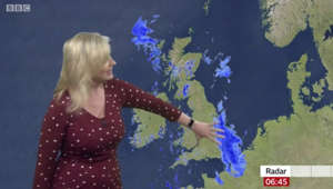 a person holding a sign: BBC Weather: Low pressure front to bring thundery showers