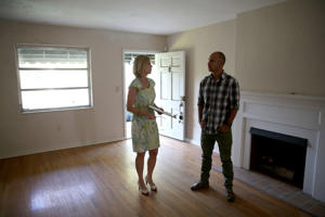 Real Estate agent Denise Madan shows prospective buyer Juan Carlos Correa a home that is listed as a short sale as he shops for a house on April 22, 2014 in Coral Gables, Florida.