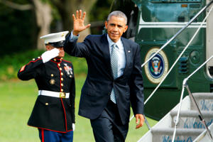 President Barack Obama waves as he arrives via Marine One helicopter at the White House in Washington October 14, 2014.