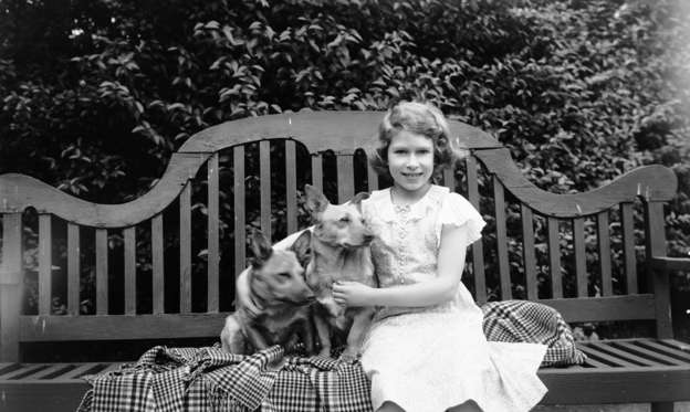 Slide 2 of 37: July 1936:  Princess Elizabeth sitting on a garden seat with two corgi dogs at her home on 145 Piccadilly, London.  (Photo by Lisa Sheridan/Studio Lisa/Getty Images)