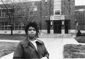 "Linda Brown Smith stands in front of the Sumner School in Topeka, Kan., on May 8, 1964.  The refusal of the public school to admit Brown in 1951, then nine years old, because she is black, led to the Brown v. Board of Education of Topeka, Kansas.  In 1954, the U.S. Supreme Court overruled the ""separate but equal"" clause and mandated that schools nationwide must be desegregated."