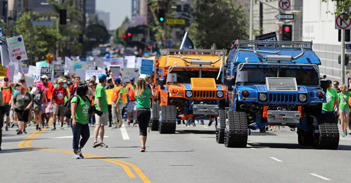 """Slide 2 of 24: Two giant electric Humvees lead thousands of people in a march and rally in downtown Los Angeles, part of the nationwide March for Science, taking place Saturday, April 22, 2017. They chanted """"Money for science and education, not for wars and climate alteration."""""""