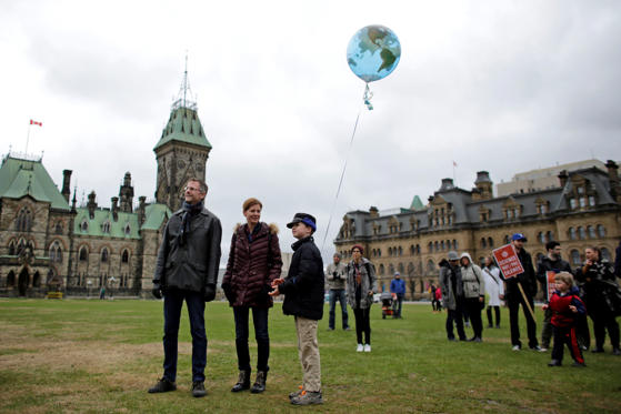 Slide 4 of 24: A child holds a globe balloon during the March for Science rally on Earth Day at Parliament Hill in Ottawa, Ontario, Canada, on Saturday, April 22, 2017. The March for Science is a nonpartisan rally bringing together scientists, science supporters, teachers and parents, along with politicians with an aim to advocate the role of science in education and informing evidence-based policies within the public interest.