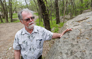 <p>Wichita State archaeologist and anthropologist Donald Blakeslee points out man-made depressions.</p>