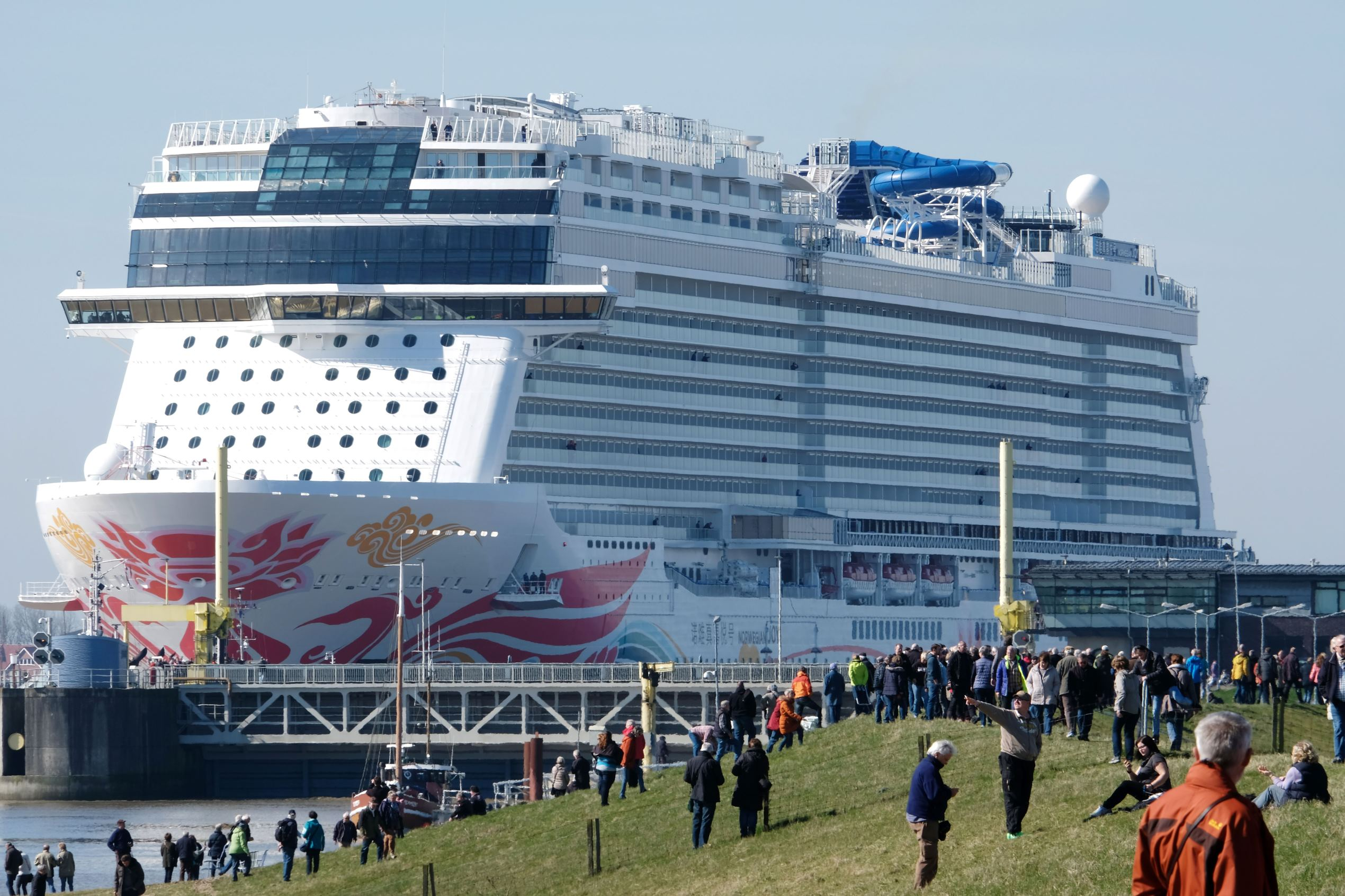 Slide 23 of 31: Spectators look on as the 'Norwegian Joy' cruise ship, previously named 'Norwegian Bliss', passes a shipping lock to make its way over the river Ems near Emden, northern Germany, on March 27, 2017. The ship of the Norwegian Cruise Line, that was built at the Meyer Werft shipyard in Papenburg, northern Germany, is made ready to enter service. Final technical and nautical tests are due to be carried out during the following days on the North Sea. / AFP PHOTO / PATRIK STOLLARZ (Photo credit should read PATRIK STOLLARZ/AFP/Getty Images