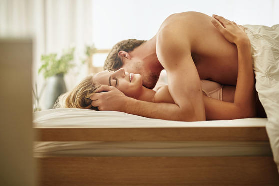 Diapositiva 1 de 42: Shot of a young couple sharing an intimate moment  in bed.