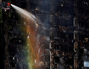 The sun creates a rainbow effect as firefighters work at the scene of a deadly blaze at a high rise apartment block in London, Wednesday, June 14, 2017. Fire swept through a high-rise apartment building in west London early Wednesday, killing an unknown number of people with around 50 people being taken to hospital.