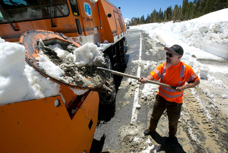 In this photo taken Tuesday, June 6, 2017, Caltrans maintenance worker Paul Jensen removes snow and dirt that is clogging the rotary blower he is operating to clear snow from Highway 120 near near Yosemite National Park, Calif.