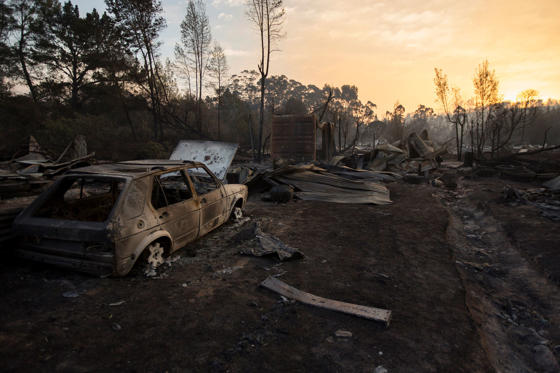 Slide 3 of 24: A vehicle and home destroyed by fire in Knysna, South Africa, Thursday, June 8, 2017. Fires fanned by high winds spread to nearby Plettenburg Bay and Knysna in the Western Cape Province killing three people, destroying homes and forcing the evacuation of up to 10,000 people. (AP Photo/Halden Krog)