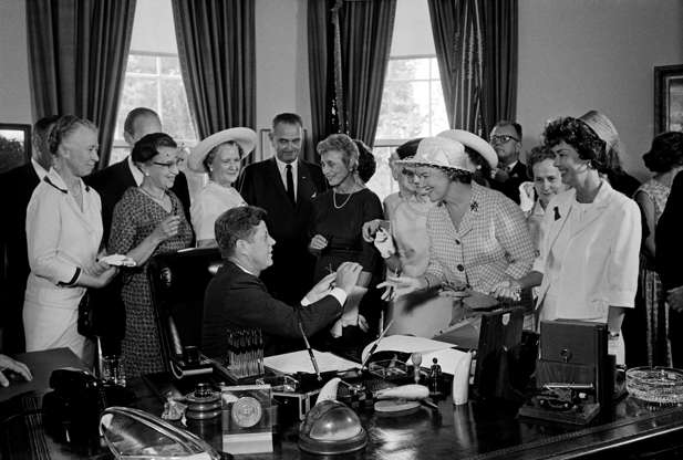 Slide 8 of 13: President Kennedy hands out pens during a ceremony at the White House today in which he signed into law a bill aimed at assuring women of paychecks equal to those of men doing the same work. Left to right: Esther Peterson, Assistant Secretary of Labor; Evelyn Christensen, National Board of YWCA; Rep. Leonor Sullivan (D-Missouri); Vice President Lyndon Johnson; Mrs. Joseph Willen, National Council of Jewish Women; Dr. Minnie Miles, National Federation of Business and Professional Women's Clubs (partially hidden); Miss Margaret Mealey, National Council of Catholic Women; Andrew Biemiller, AFL-CIO Official; Rep. Edith Green (D-Oregon); and Mrs. Garlyn Davis.