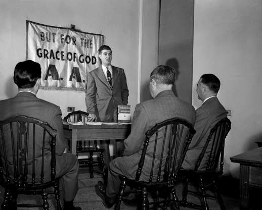 Slide 4 of 13: After three months without a drink, John finds himself an Alcoholics Anonymous crusader, helping the good work of saving others by telling of his successful fight. Photograph circa 1950.