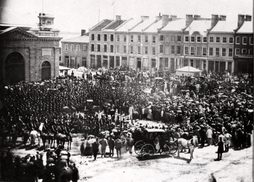 Slide 2 of 11: Image Caption: People crowded into Kingston, Ontarioâs Market Square on July 1, 1867, as the confederation of Canada was proclaimed.