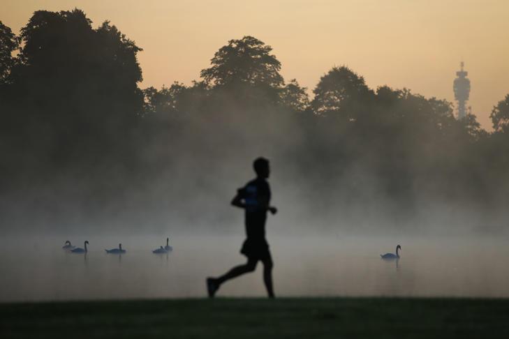 A jogger runs past the Round Pond as the sun rises at Kensington Gardens