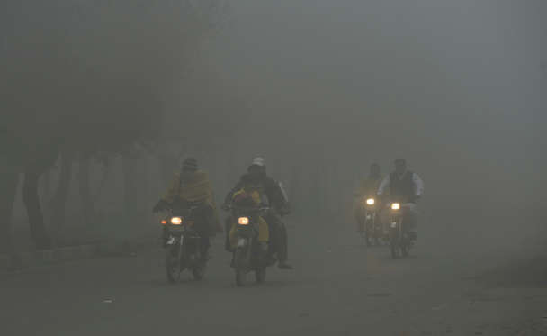 Slide 8 of 26: Pakistani motorcyclists ride along a street amid heavy smog in Lahore on Nov. 9, 2017. Flights were cancelled, school times pushed back and hospitals flooded as air pollution inundated Pakistan's second largest city Lahore. The fast-developing country suffers from some of the worst air pollution in the world, thanks to its giant population navigating poorly maintained vehicles on its roads and unchecked industrial emissions along with seasonal crop burning.