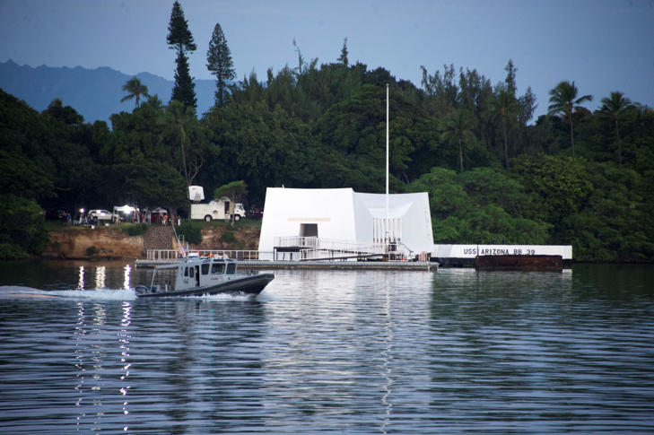 A morning patrol boat goes past the USS Arizona Memorial before a ceremony commemorating the 75th anniversary of the attack on Pearl Harbor at Kilo Pier on December 07, 2016 in Honolulu, Hawaii.