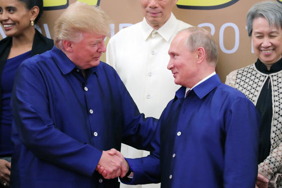 Slide 3 of 36: US President Donald Trump and Russia's President Vladimir Putin (L-R front) shake hands during a family photo ceremony at the 2017 Asia-Pacific Economic Cooperation (APEC) summit.