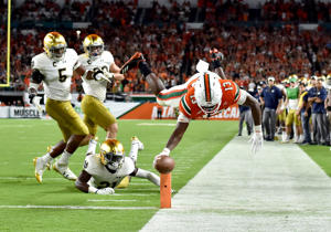 Miami Hurricanes quarterback DeeJay Dallas (13) dives over for a touchdown past Notre Dame Fighting Irish safety Jalen Elliott (21) during the second half against on Nov. 11 in Miami Gardens, FL.