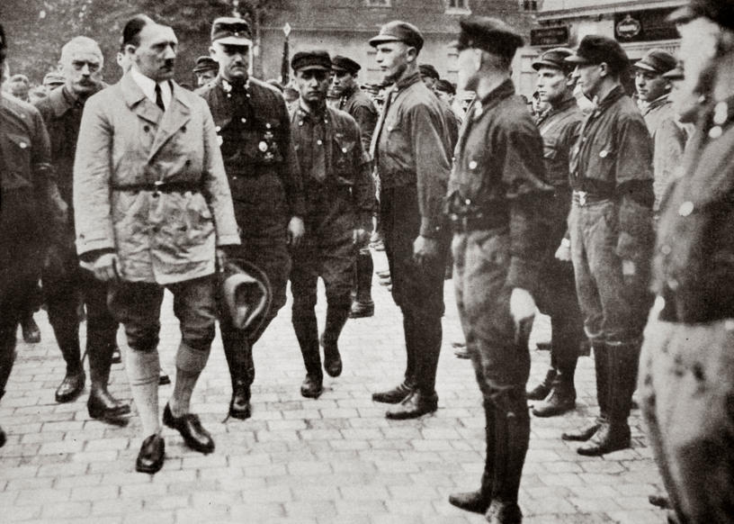 Slide 55 of 100: Hitler inspecting a group of SA Members during World War II, Germany, 1939-1945. Founded in c1919, the Sturmabteilung (SA) was the paramilitary wing of the Nazi party. Its members were known as the 'Brownshirts' because of the colour of their uniforms. The SA played an important part in Hitler's (1889-1945) rise to power in Germany but its significance was effectively ended when its leaders were killed in the 'Night of the Long Knives' in 1934, with the rival Schutzstaffel (SS) taking over its role. Artist Unknown.