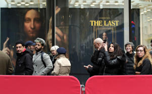 "Visitors to Christie's wait outside in a line to view Leonardo da Vinci's ""Salvator Mundi"", Tuesday, Nov. 14, 2017, in New York. The painting is expected to sell at auction for $100 million on Wednesday."