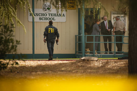 FBI agents are seen behind yellow crime scene tape outside Rancho Tehama Elementary School after a shooting in the morning on November 14, 2017, in Rancho Tehama, California Four people were killed and nearly a dozen were wounded, including several children, when a gunman went on a rampage at multiple locations, including a school in rural northern California.