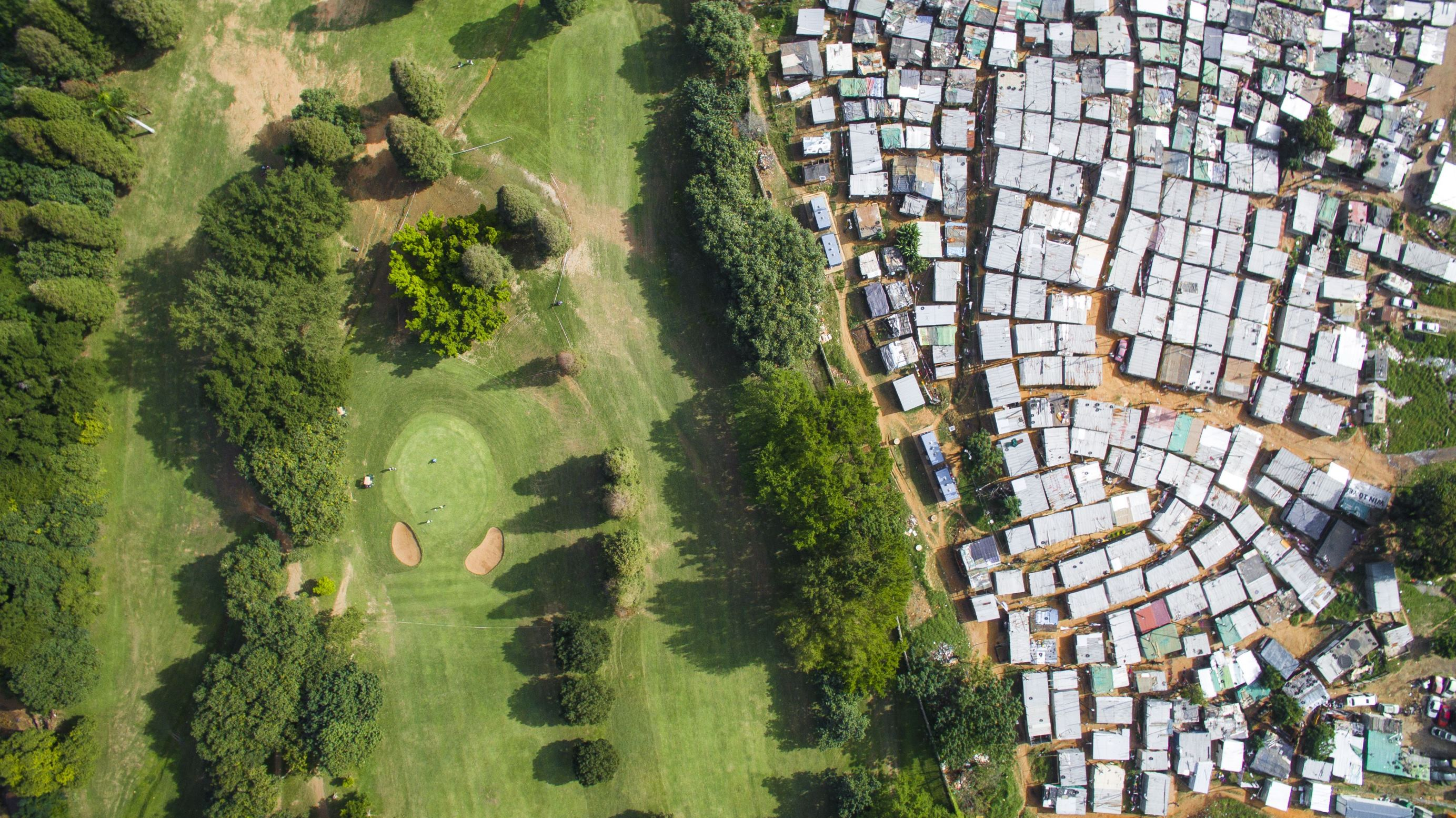 Slide 66 of 100: Papwa Sewgolum Golf Course is located along the lush green slopes of the Umgeni River in Durban. A sprawling informal settlement exists just metres from the tee for the 6 hole. A low-slung concrete fence separates the tin shacks from the carefully manicured fairways