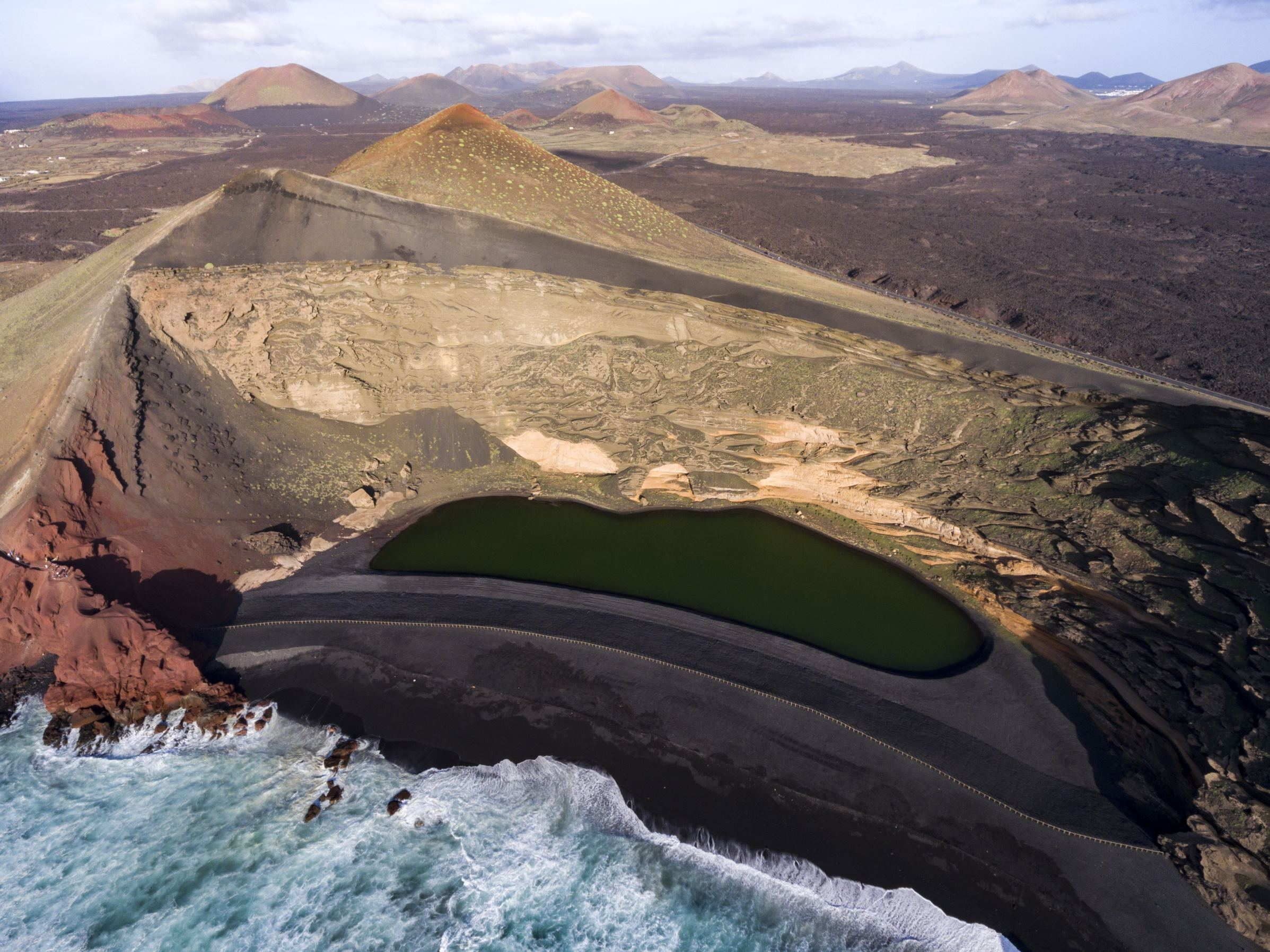 Slide 81 of 100: Much of Lanzarote has been shaped by devastating volcanic eruptions during the 18th century, leaving behind a lunar type landscape, black beaches and locations such as the Timanfaya National Park, which is home to an active volcano that gives the park its name.