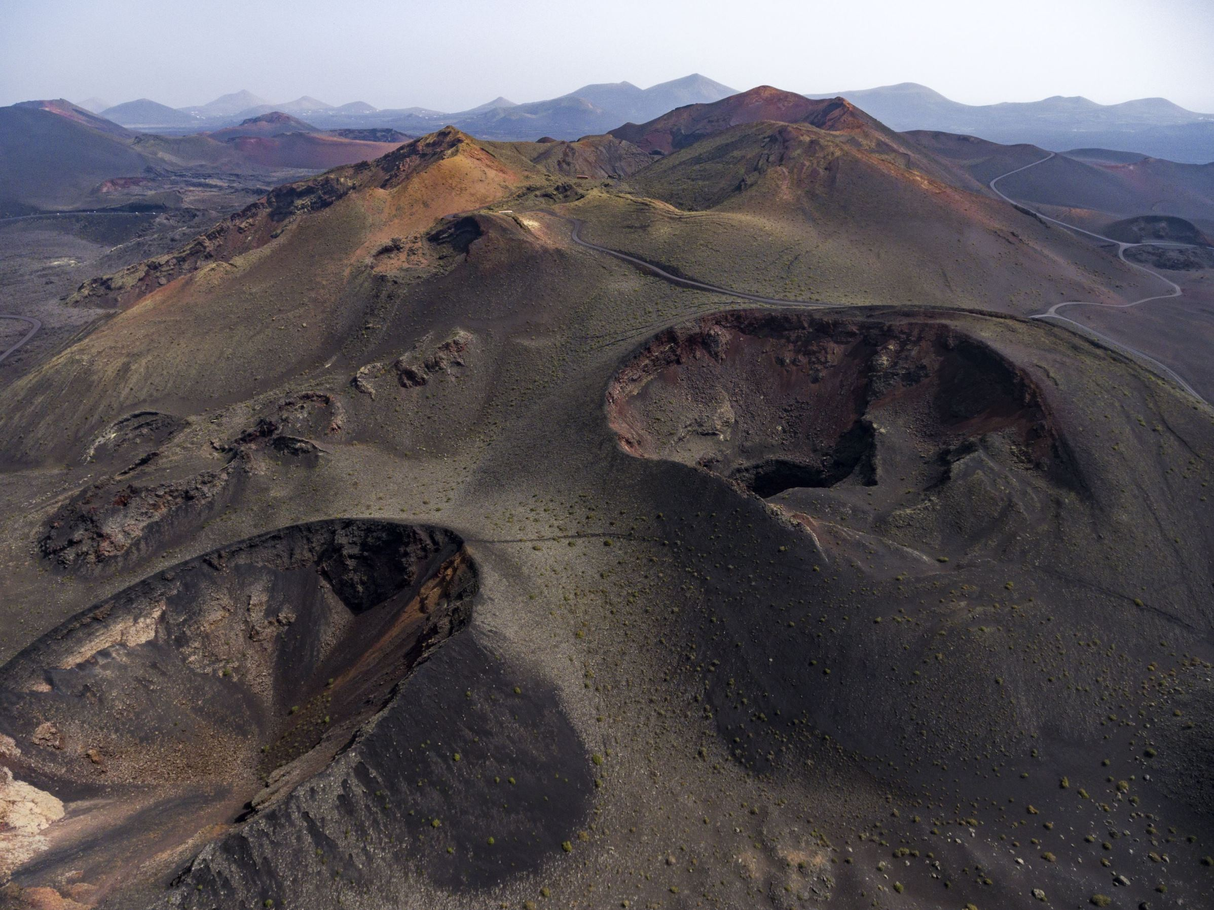 Slide 58 of 100: Much of Lanzarote has been shaped by devastating volcanic eruptions during the 18th century, leaving behind a lunar type landscape, black beaches and locations such as the Timanfaya National Park, which is home to an active volcano that gives the park its name.