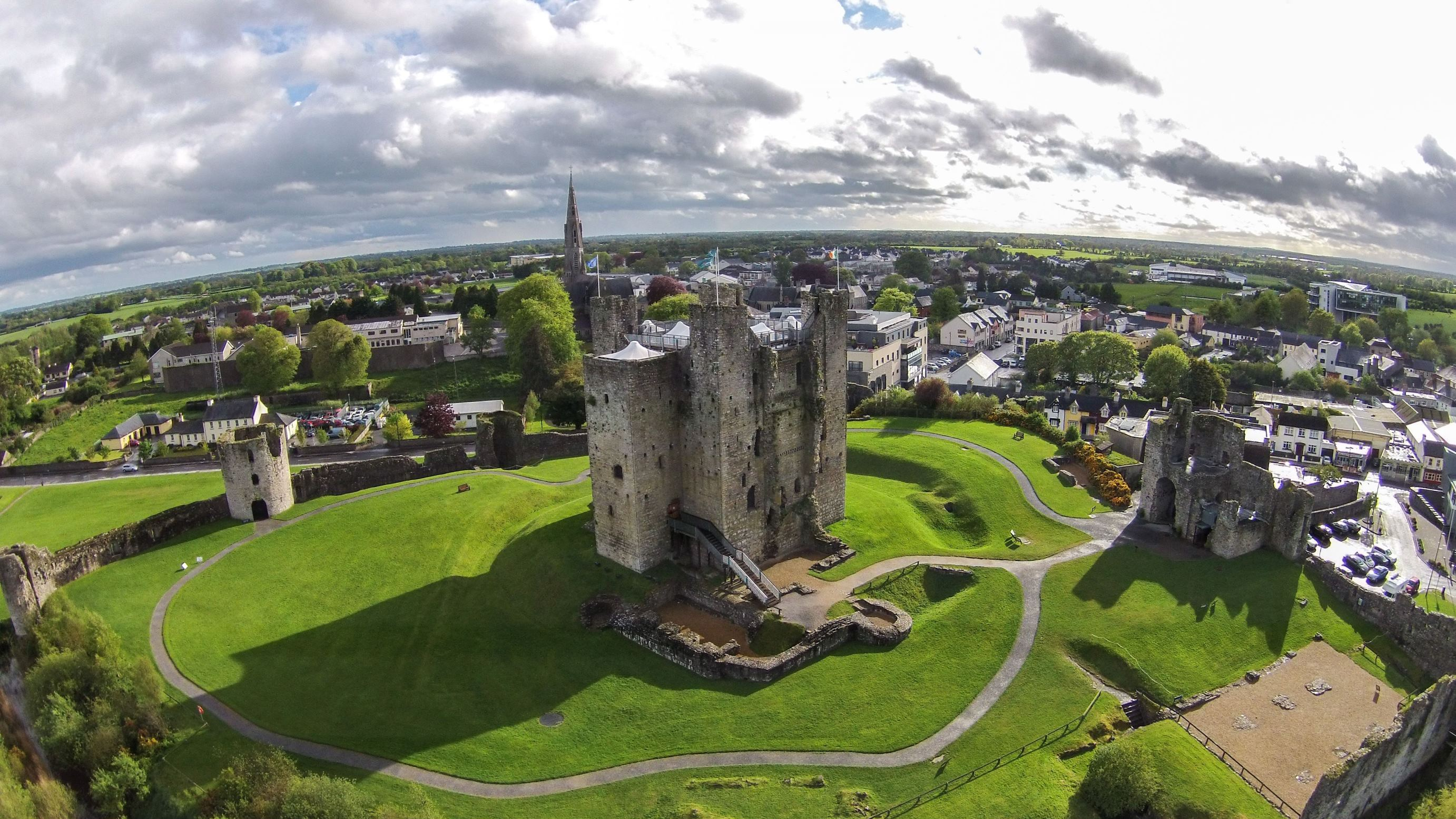 Slide 78 of 100: Bird's-eye-view images of Castle Ward (otherwise known as Winterfell Castle in Game of Thrones) alongside Trim Castle can be seen. Meanwhile, drone images of hills, coastlines and beaches can also be seen.