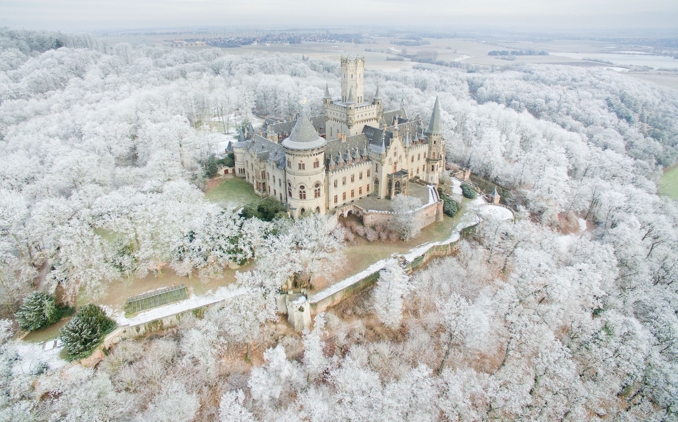 Slide 36 of 100: TOPSHOT - Aerial view taken on January 18, 2017 with a drone shows the Marienburg Castle near Pattensen, northern Germany, standing amidst a snow-covered forest. / AFP / dpa / Julian Stratenschulte / Germany OUT (Photo credit should read JULIAN STRATENSCHULTE/AFP/Getty Images)