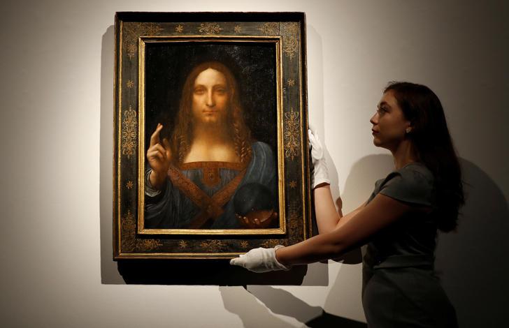 "Members of Christie's staff pose for pictures next to Leonardo da Vinci's ""Salvator Mundi"" painting."