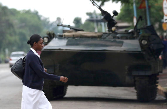 Slide 3 of 28: A woman walks past an armoured vehicle in Harare, Zimbabwe, November 18, 2017.