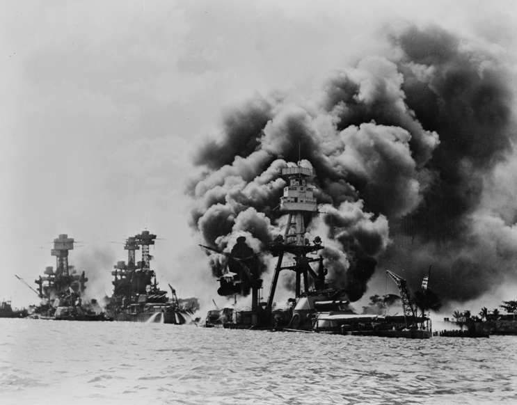 Slide 27 of 100: Three stricken US battleships. Left to right, West Virginia, Tennessee and Arizona after the Japanese attack on Pearl Harbour in World War II, 1941. (Photo by: Universal History Archive/UIG via Getty images)