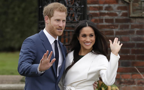 Slide 1 of 5: Britain's Prince Harry and his fiancee Meghan Markle pose for photographers during a photocall in the grounds of Kensington Palace in London, Monday Nov. 27, 2017. Britain's royal palace says Prince Harry and actress Meghan Markle are engaged and will marry in the spring of 2018.
