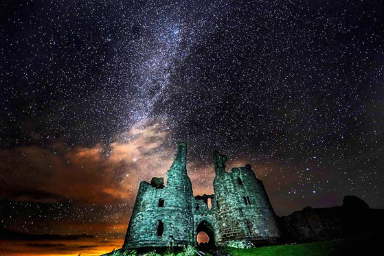Slide 1 of 75: Caption: The great gatehouse of Dunstanburgh Castle ruins in Alnwick, Northumberland, under a starry sky.