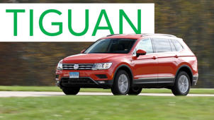 a car parked in front of a sign: 2018 Volkswagen Tiguan Road Test