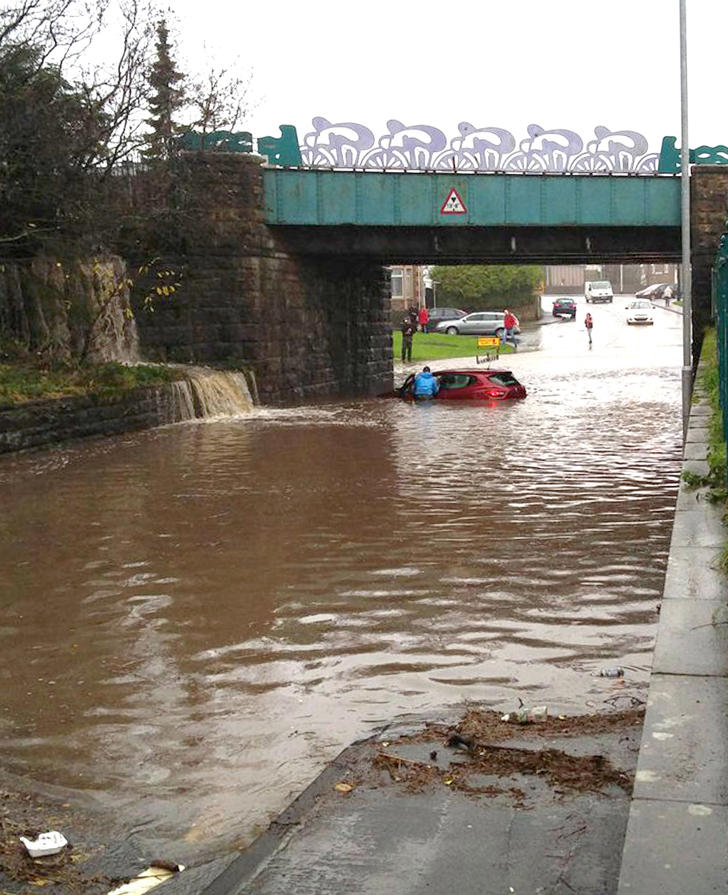 Handout photo from Twitter user Martin A of a car stuck in flood water under a railway bridge in Seaton, Cumbria, following heavy rain on Wednesday.
