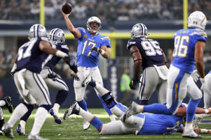 Philip Rivers (17) of the Chargers passes under pressure from DeMarcus Lawrence of the Cowboys and David Irving (95) of the Cowboys on Nov. 23 in Arlington, Texas. Chargers won 28-6.