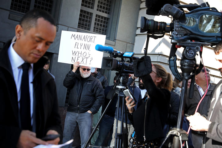 A handful of demonstrators held signs as they joined journalists outside the Courthouse